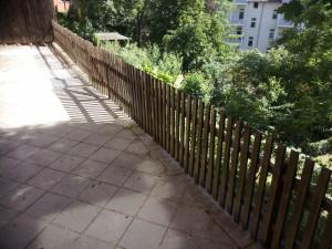 Der Holzzaun mit Tür, der durch einen entsprechenden Zaun aus verzinktem Stahl zu ersetzen ist.